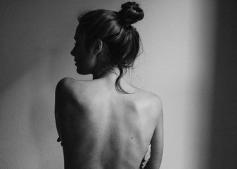 young woman with bare back towards camera intimate studio black and white