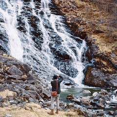 Young man photographing a waterfall