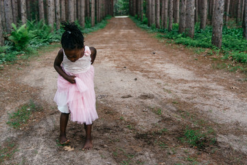 Black girl in pink dress stepping on a leaf on the ground in a forest