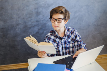 Teen boy reading book and use laptop at home