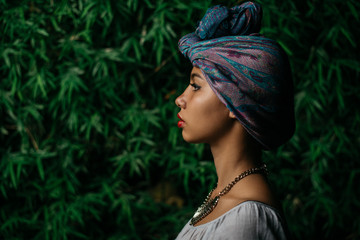 Portrait of a Beautiful Stylish Woman with Turban Standing Against the Leafy Green Background