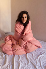 Young woman covered with pink sheets in her bed