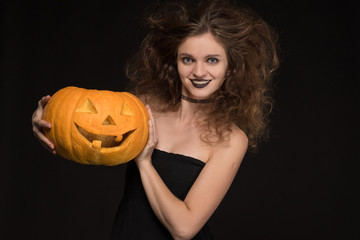 Beautiful girl with a make-up as a witch smiles and holds an orange pumpkin on a black background for the holiday of Halloween
