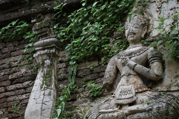 400 years old ruined ancient standing and praying of male angel statue at Chiangmai covered with green leaf, Thailand, buddha statue without some of body part, historical decorated wall temple