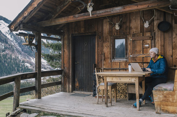Man working outdoors on laptop computer in mountain cabin
