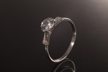 ring in gold with gemstone and diamond, classic jewelry band with gem in background black
