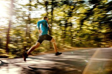 blurred motion male runner running on forest road in sunlight