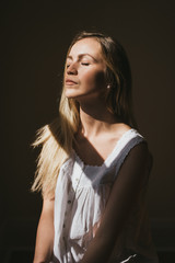 Young woman meditating by window light