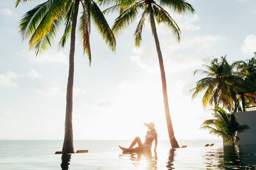 Attractive Woman Sitting Alone By Hotel Pool at Sunset on Tropical Beach