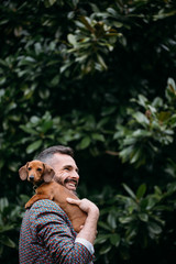 Portrait of man at the park holding his dog