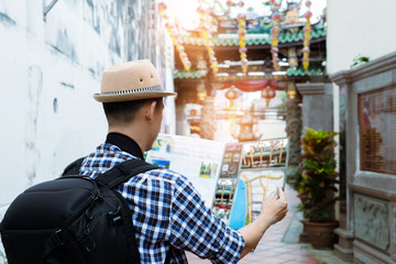 Tourist and map,travel concept.Man checking destination from a map with chinese shrine in background.