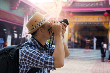 Tourist sightseeing old town, travel concept.Street photographer taking a picture of old shrine chinese temple in phuket old town with vintage camera ,side view.