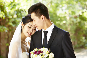 outdoor portrait of a happy and loving asian newly-wed couple