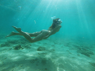 Skinny fit girl swimming underwater