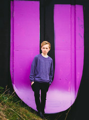 Teenager standing in front of a painted U on a wall