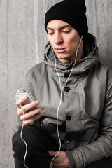 Portrait of young hip male using phone with headphones.