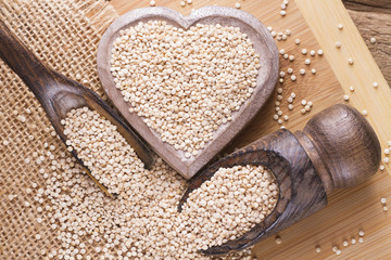 pile of quinoa seeds in container on wood