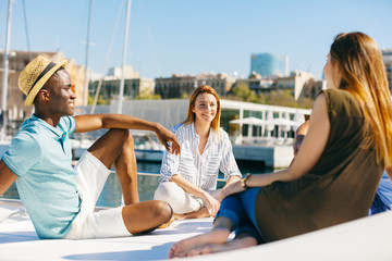 Young multiethnic friends having fun on a sunny day on a luxurious yacht.