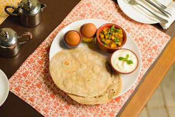 Traditional Nepali Indian breakfast with hard boiled eggs, prata bread, lentil curry and curd yogurt, served in Kathmandu