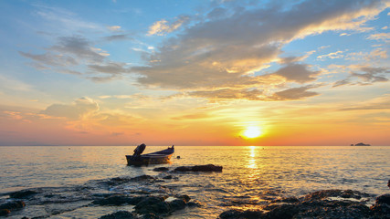 Small boat floating on the sea during sunset