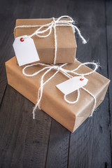 Two overlaid presents with labels - Gift boxes, wrapped with brown paper and white flax rope, having tags attached with space for your text, on an old wooden table.