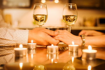 Couple drinking wine and holding hands.