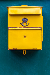 Close up of a classic yellow public postal mail box with a mail symbol, mounted on a blue wall outdoors.