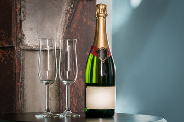 Indoors still life shot of a unopened champagne bottle and two empty glasses on a table. Label with copy space.