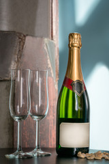 Still life shot of a unopened champagne bottle and two empty glasses on a table with snacks. Label with copy space.