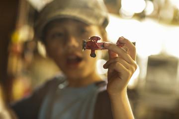 niño jugando con un avión de madera, el barón rojo