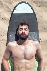 Handsome Surfer Man Relaxing on the Beach