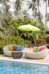 Swimming pool and rattan daybeds in a tropical garden, Thailand