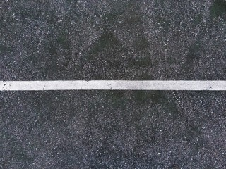 Abstract white lines painted on distressed asphalt concrete surface