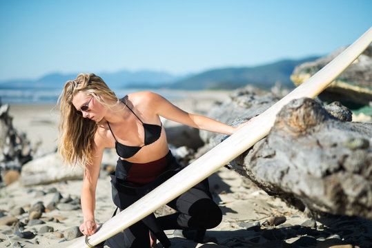 Young beautiful blonde surfer chick waxes her surfboard.