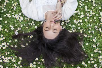 Woman lying in daisies