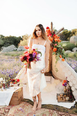 Bohemian bride standing outside of the teepee
