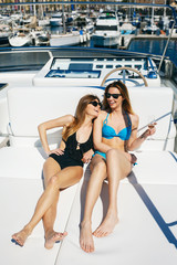 Young women tanning on a luxurious yacht couch.