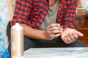 man painting his own draws at his art studio