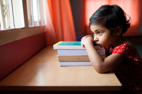 Bored little girl resting on a pile of books