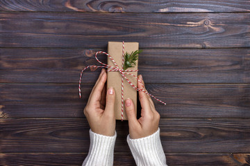 Female hands wrapping christmas gift box above wooden table. Top view