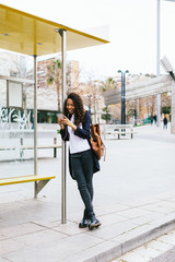 Young african american woman using her smart phone whilst waiting for the bus.