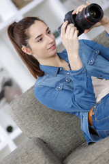 young woman holding modern camera