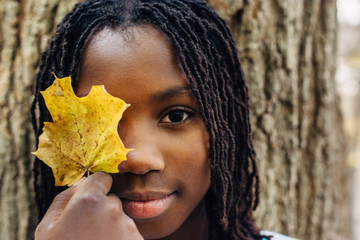 Black girl holding a yellow autumn leaf