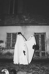 Family of ghosts in front of their home in black and white