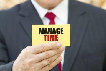 Businessman showing a card with text MANAGE TIME