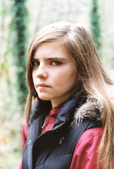 somber teenager in vest looking at camera
