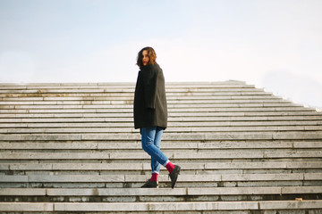Beautiful young woman in a black coat standing on the stairs, looking at the camera.