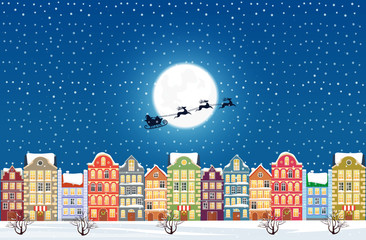 Santa Claus flies over a decorated snowy old city town at Christmas eve.