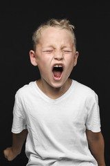 Little blond boy is screaming or cries loud against black background