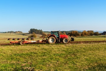 Red tractor pole field. Autumn field work. Life on the farm. Agricultural landscape in the Czech Republic.